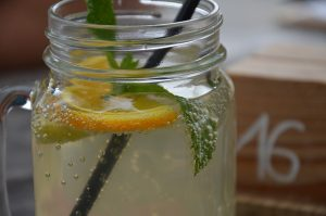 A jar of water with slices of lemon and a plastic straw