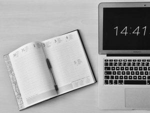 A pen, notebook planner and a laptop showing what time it is