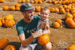 Father and son in a field of pumpkins