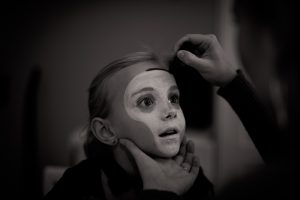 Halloween costumes from leftover moving boxes- a boy getting his face painted