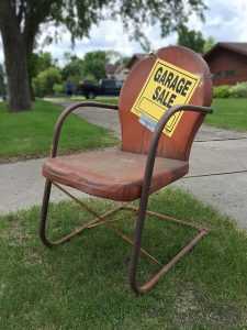 "Rusty chair with a sign ""garage sale"""