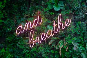 A neon sign saying- and breathe