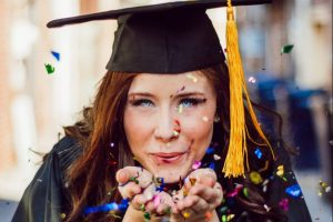 Graduation - a girl blowing some glitter towards the camera