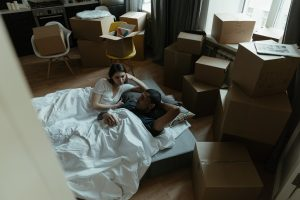 couple on the mattress surrounded by packing boxes
