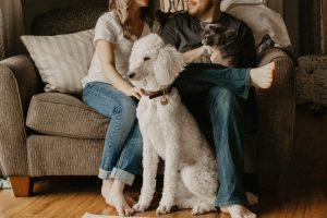 couple sitting with a dog and cat