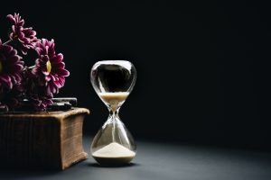 an hourglass next to flowers