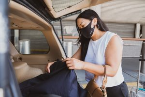 woman putting a bag in the car
