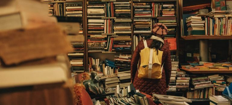 Woman looking at shelves of books.