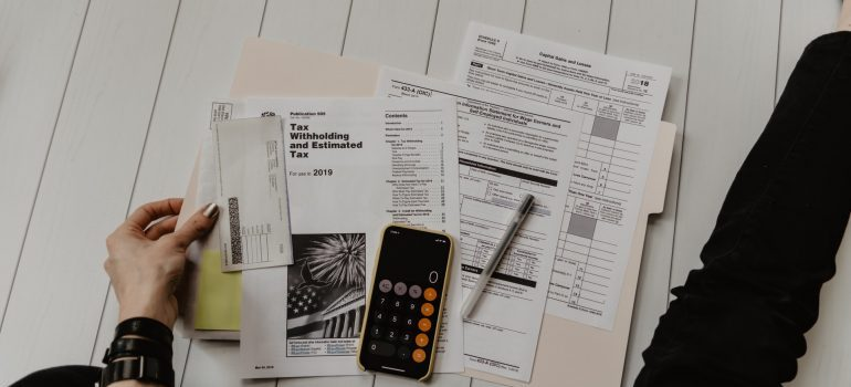 A person surrounded by papers and a calculator