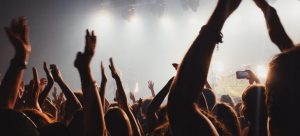 people dancing at the concert with their hands in the air