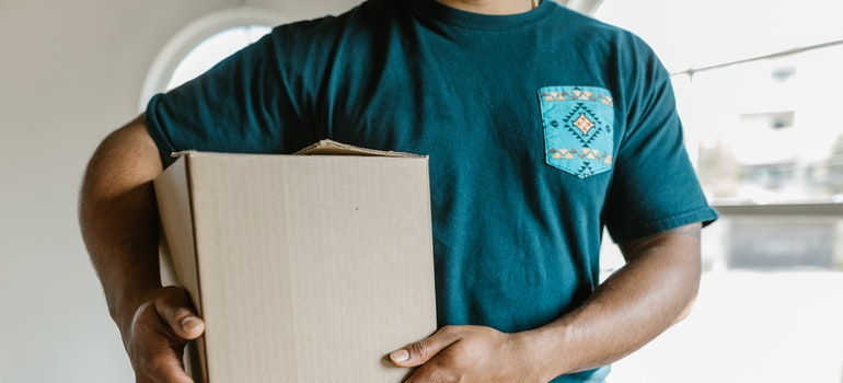 A man from the moving company is carrying a box.