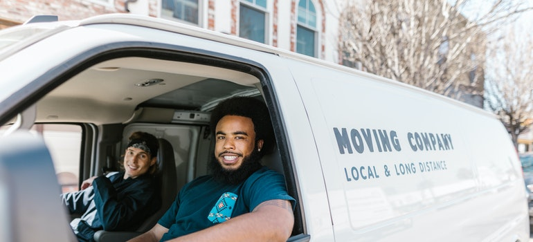 Two men from the moving company are waiting in the moving van.