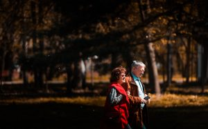 A retired couple is walking through one of many parks in San Antonio, with brown fall leaves.