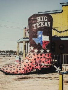 A big cowboy boot in front of one of the restaurants on Route 66 stopover, decorated with Texan signs.