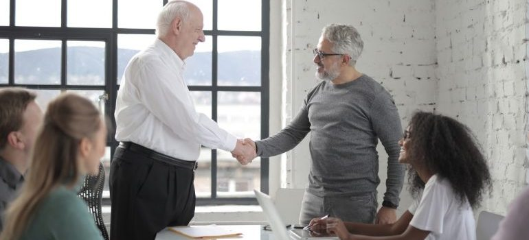 Two people shake hands, after concluding a business agreement