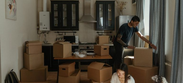 A man and a woman are packing kitchen appliances