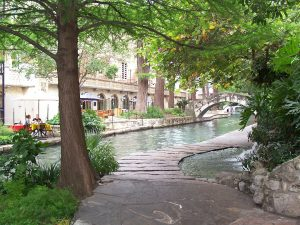 A scene from San Antonio, with path walk over the river, a bridge, threes, and house with people sitting outside a café.