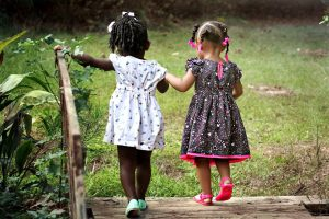Two small girls are holding hands and walking over the bridge, in one of San Antonio parks.
