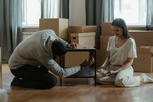 The man unscrews the legs of the table, and the woman sits on the floor next to the table, to avoid damaging furniture while moving to San Antonio.