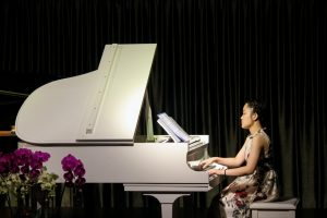 A woman is playing piano on the stage.