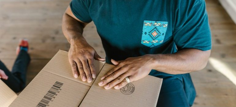 A professional mover closes the box during the moving process.