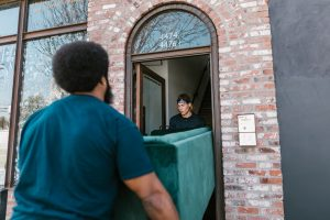 Two movers carry the couch through the door of the building.